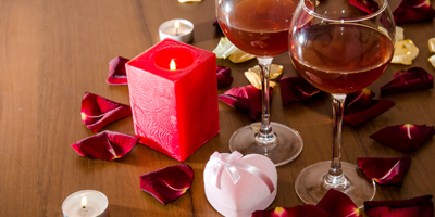 Celebration event - Valentine's Day - Wine, candles, and red petal roses on table